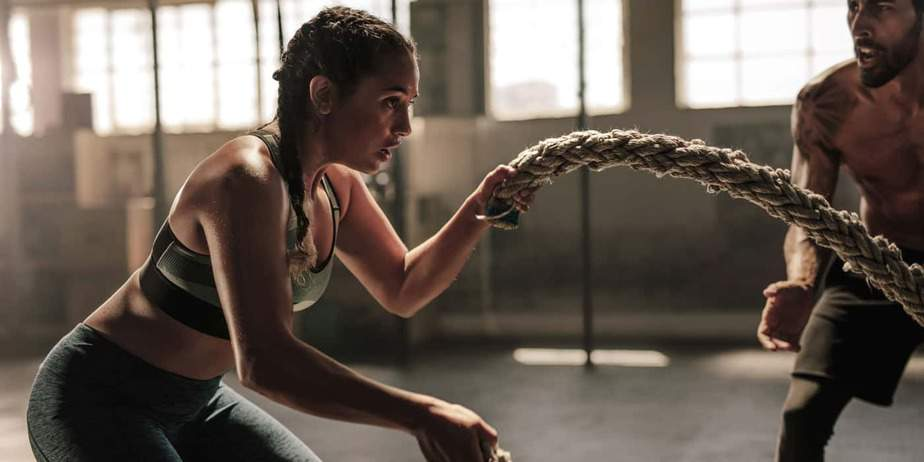 Young woman working out on battle ropes.